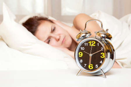 woman resting: Sleeping woman resting in bed with alarm clock ready to wake her in the morning Stock Photo