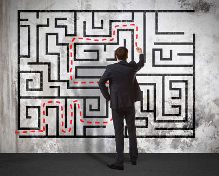 difficult task: Business concept. Back view of businessman drawing labyrinth on wall Stock Photo