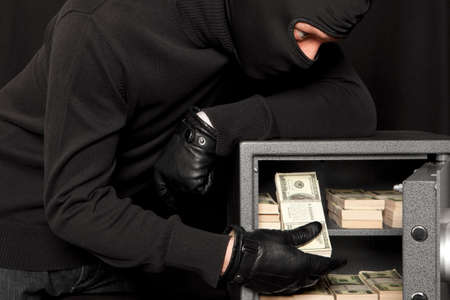 scammer: Thief burglar stealing money during home safe codebreaking