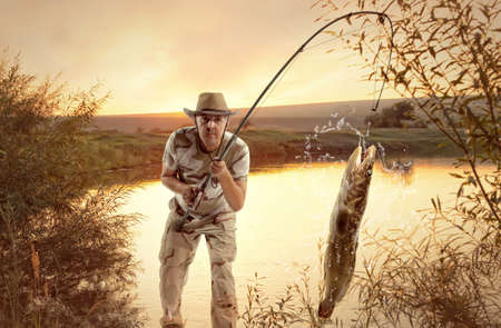 burbot: Burbot. Man fishing  in the river at sunset Stock Photo