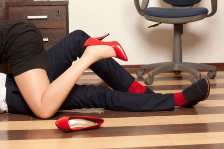 Adultery. Low section of business couple getting intimate on floor in office