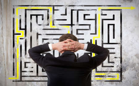 solved maze puzzle: Business concept. Back view of businessman looking at a maze on wall Stock Photo
