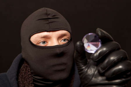 felon: Thief. Man in black mask with a big diamond.Focus on thief