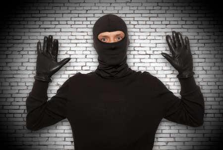 coger: Ladrón con pasamontañas atrapado en frente de la pared