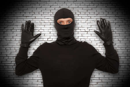 thieves: Thief with balaclava caught in front of the wall