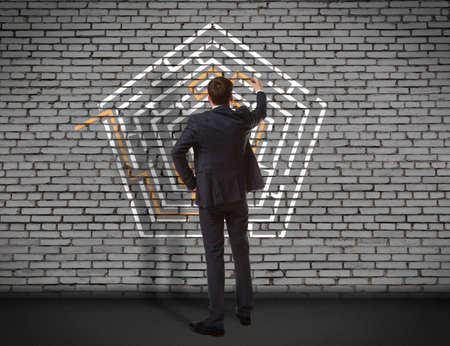 difficult mission: Business concept. Back view of businessman drawing labyrinth on wall Stock Photo