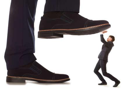 conflicto: Pequeño empresario atendidos bajo pierna grande su jefe, aislado en fondo blanco