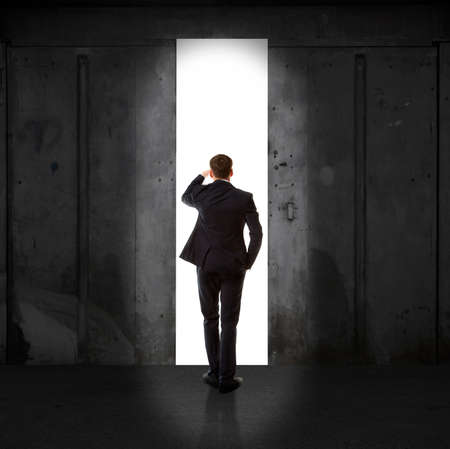 Prodigy: Infinity. Rear view of a businessman standing in front of the exit light