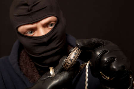 felon: Thief. Man in black mask with a silver bracelet. Focus on bracelet Stock Photo