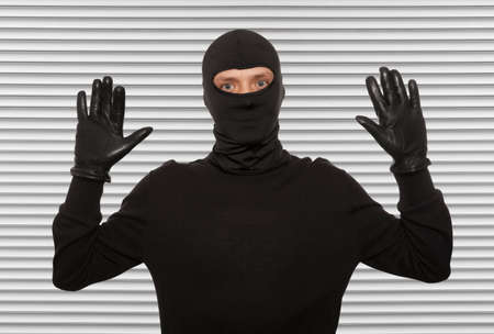 criminality: Thief with balaclava caught in front of the wall