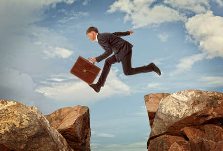 running man: Young businessman jumping over rocks with gap concept