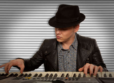 play popular: Man in the hat playing on a synthesizer