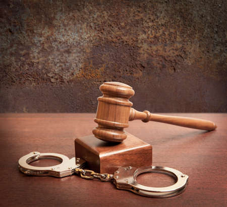 restraints: Gavel and handcuffs on wooden background