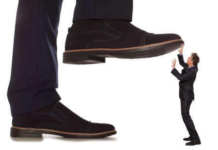 patron: Pequeño empresario atendidos bajo pierna grande su jefe, aislado en fondo blanco