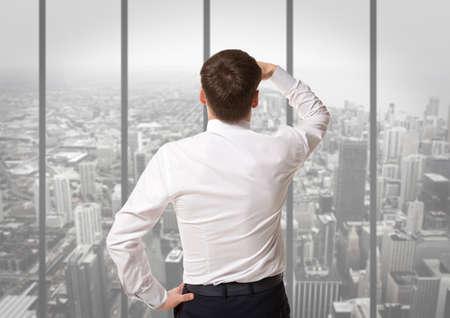purposeful: Businessman standing over skyscraper and purposefully looking away
