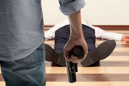 corpse: Man holding gun against a corpse background