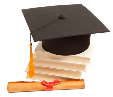 Graduation hat, book and diploma isolated on white