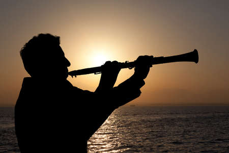 woodwind instrument: Trumpeter. Man playing on oboe against the background of sunset