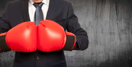red gloves: Businessman in red boxing gloves on background