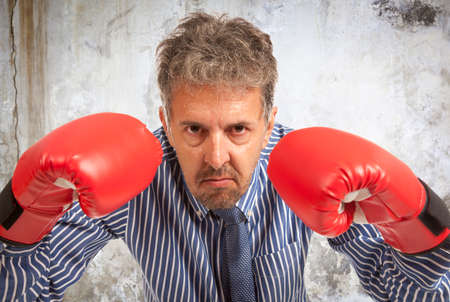 kick boxing: Businessman in red boxing gloves on background