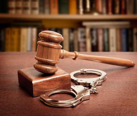Hamer en handcuffs op houten achtergrond
