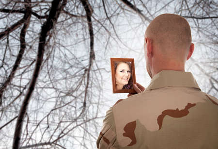 Soldier looks at the picture of the bride photo