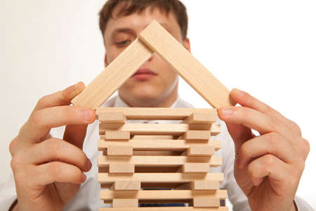 grows: Businessman building tower of wooden blocks Stock Photo