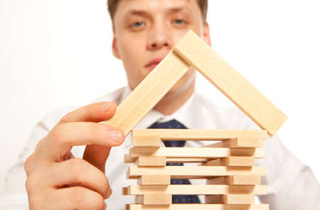 Inventor.  Businessman building tower of wooden blocks Stock Photo