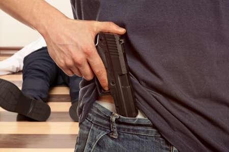 pistola: Hombre que sostiene el arma contra un fondo cadáver