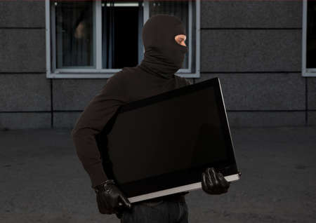 looting: Thief with balaclava stealing computer monitor or television