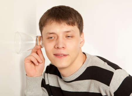 snooping: Man spying by listening through wall with glass Stock Photo