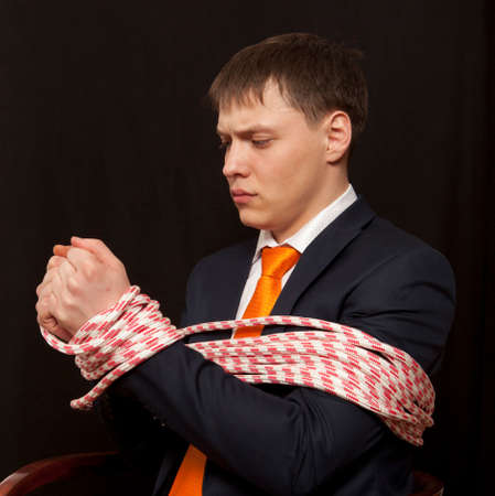 tied in: Businessman with hands tied in ropes