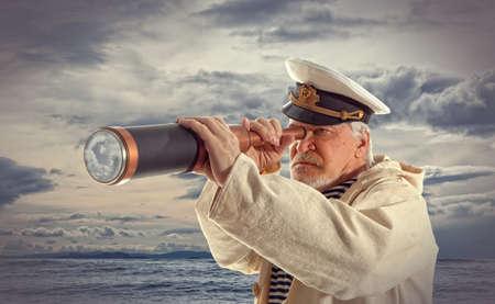 hombre viejo: El capitán mira a través de un telescopio Foto de archivo