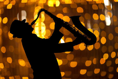 woodwind instrument: Saxophonist. Man playing on saxophone against the background of beautiful light