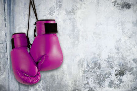 Pair of purple boxing gloves hanging on wall Archivio Fotografico