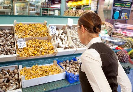 produce departments: Woman buys raw mushroom in market. Woman looking to fresh mushroom in supermarket