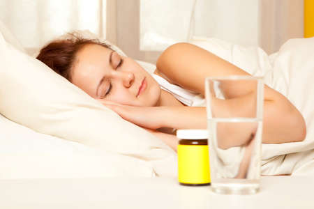 sleeping tablets: Female in bed at home caught cold, feeling bad, taking medicines, sleeping