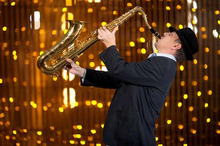 Saxophoniste. L'homme joue au saxophone sur fond de belle lumière