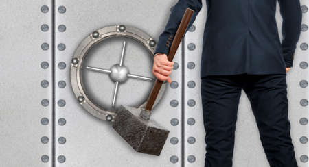 impediment: Determined businessman with hammer in hands on the background safe