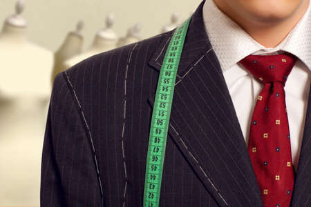measured: Tailor concept.  Businessman getting measured by a tailor
