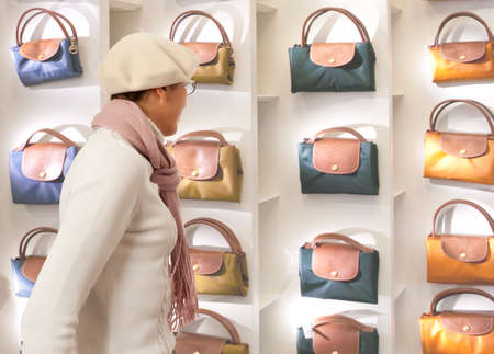 chooses: Shopping woman chooses ladys handbag in store. Woman looking to ladys handbag or shop window.