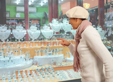 jewel: Woman looking to showcase or shop window. Shopping woman chooses jewelry in store