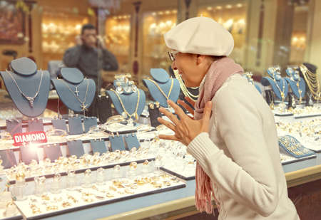fake diamond: Woman looking to showcase or shop window. Shopping woman chooses jewelry in store