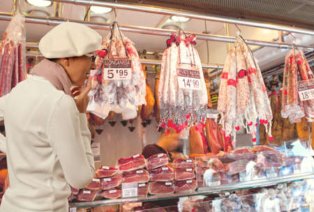 produce departments: Woman buys smoked sausage in market. Woman looking to sausage in supermarket