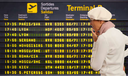 time table: Woman looking to departure board at airport