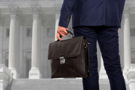 column: The lawyer with a briefcase is on against the courthouse Stock Photo