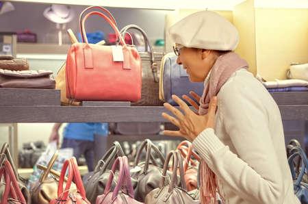 personal shopper: Shopping woman chooses ladys handbag in store. Woman looking to ladys handbag or shop window.