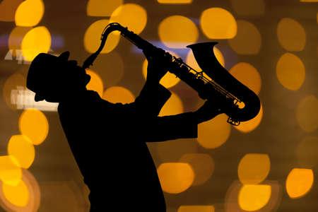 saxof�n: Saxofonista. Hombre que juega en el saxof�n en el contexto de la hermosa luz Foto de archivo