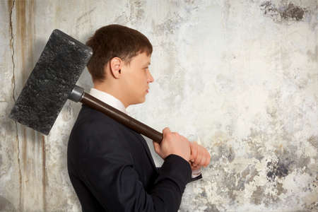 hammer: Determined businessman with hammer in hands on the background wall Stock Photo