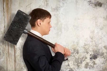 martillo: Hombre de negocios resuelto con el martillo en las manos en la pared de fondo Foto de archivo